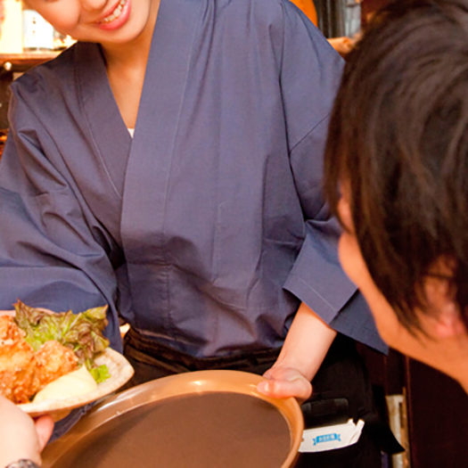 料理を運ぶ和服の女性